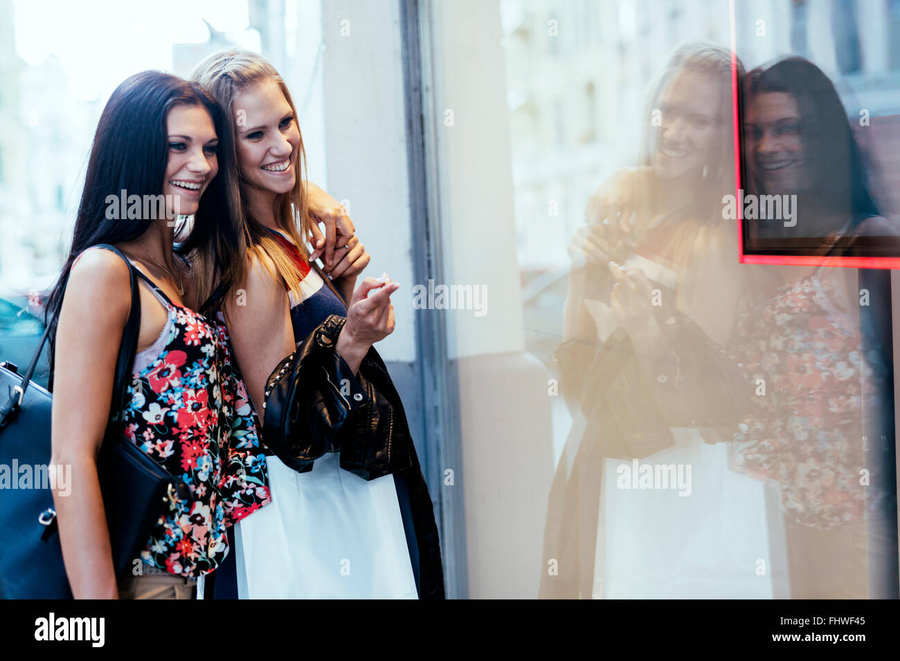 Two beautiful women shopping and looking at storefronts - Stock Image