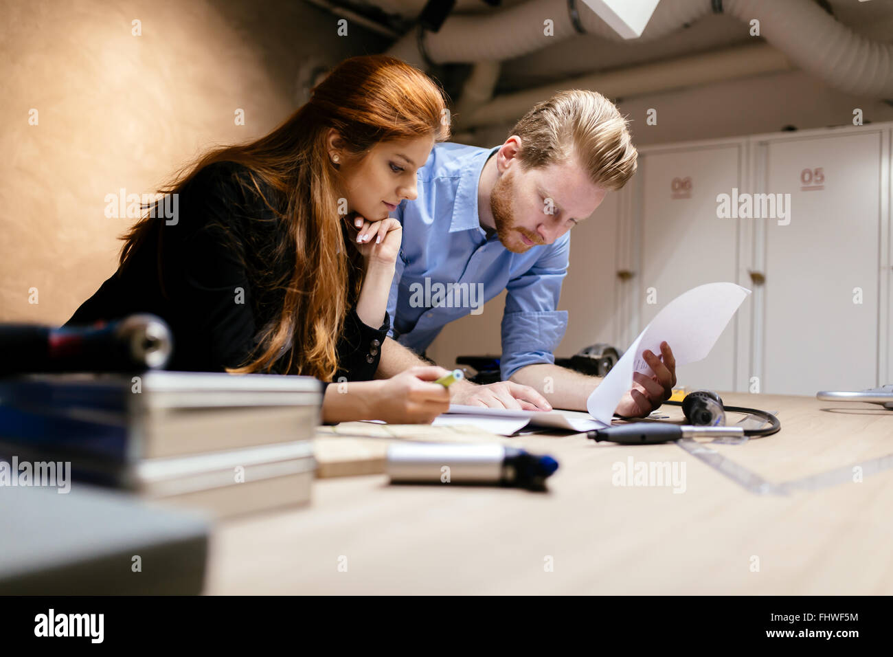 People working in modern beautiful workshop with professional equipment at hand - Stock Image