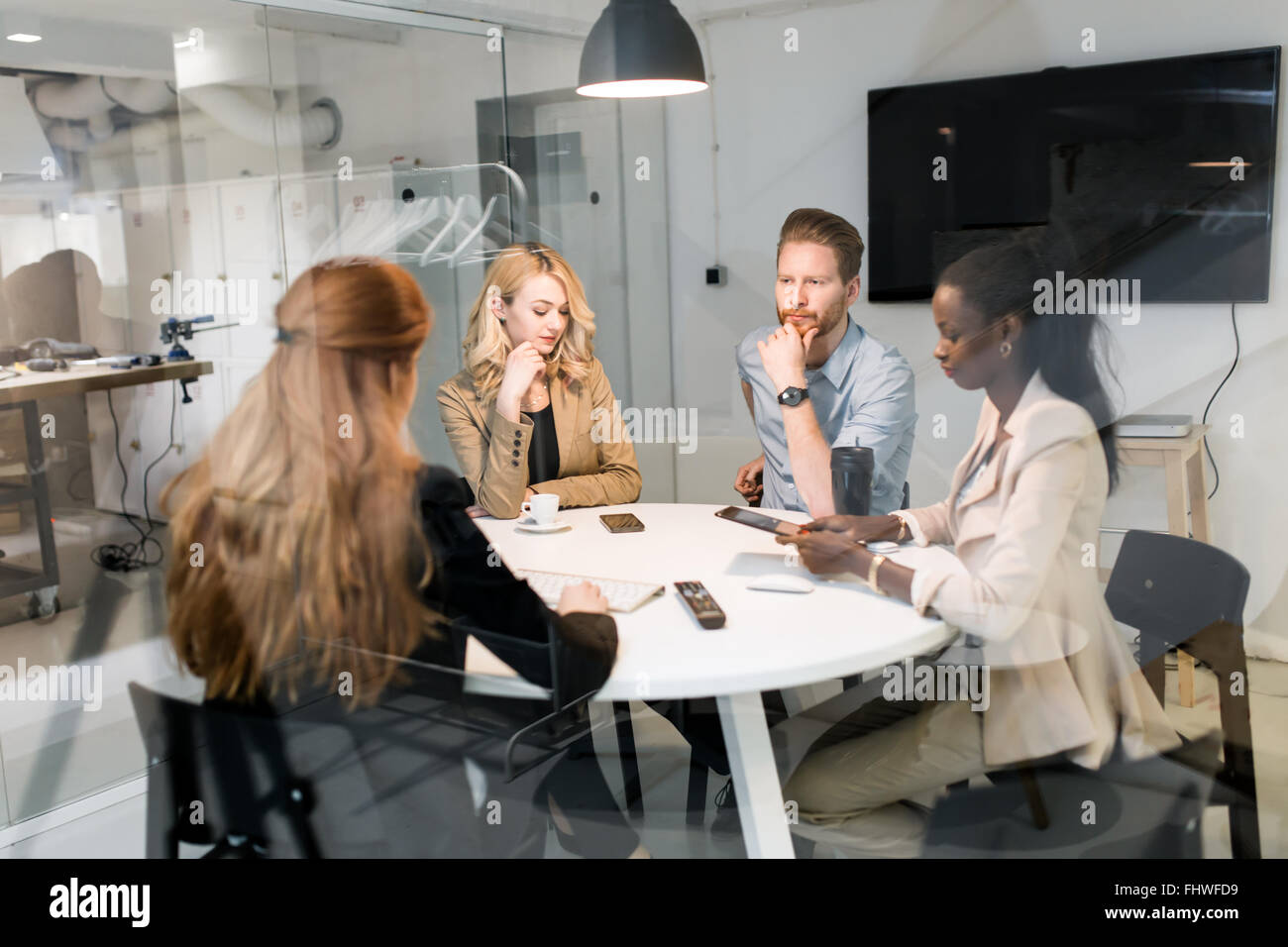 Business people board meeting in modern office while sitting at round table - Stock Image