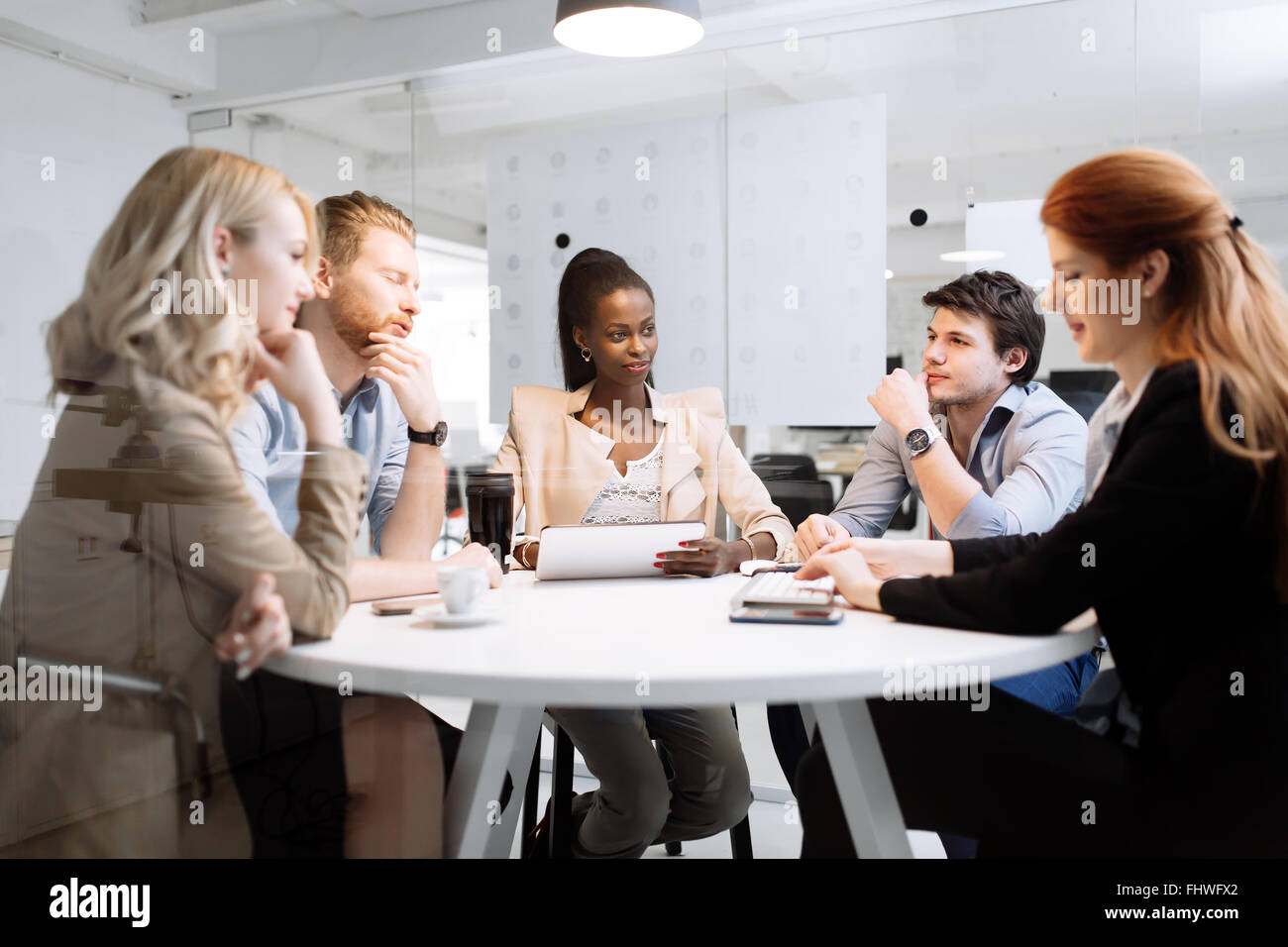 Group of business people sitting at desk and discussing