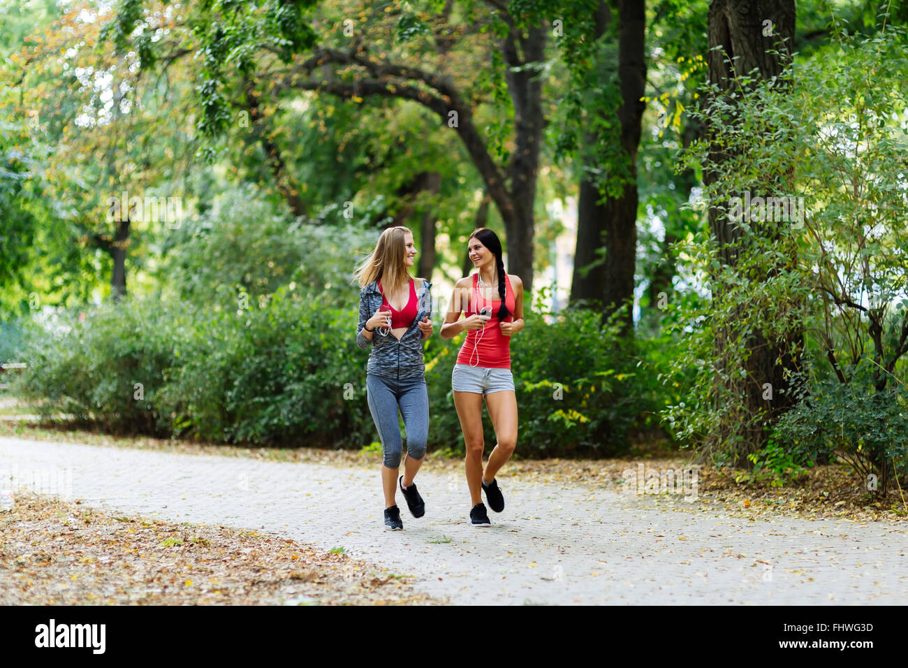 Two beautiful women jogging in park and keeping their bodies in shape - Stock Image