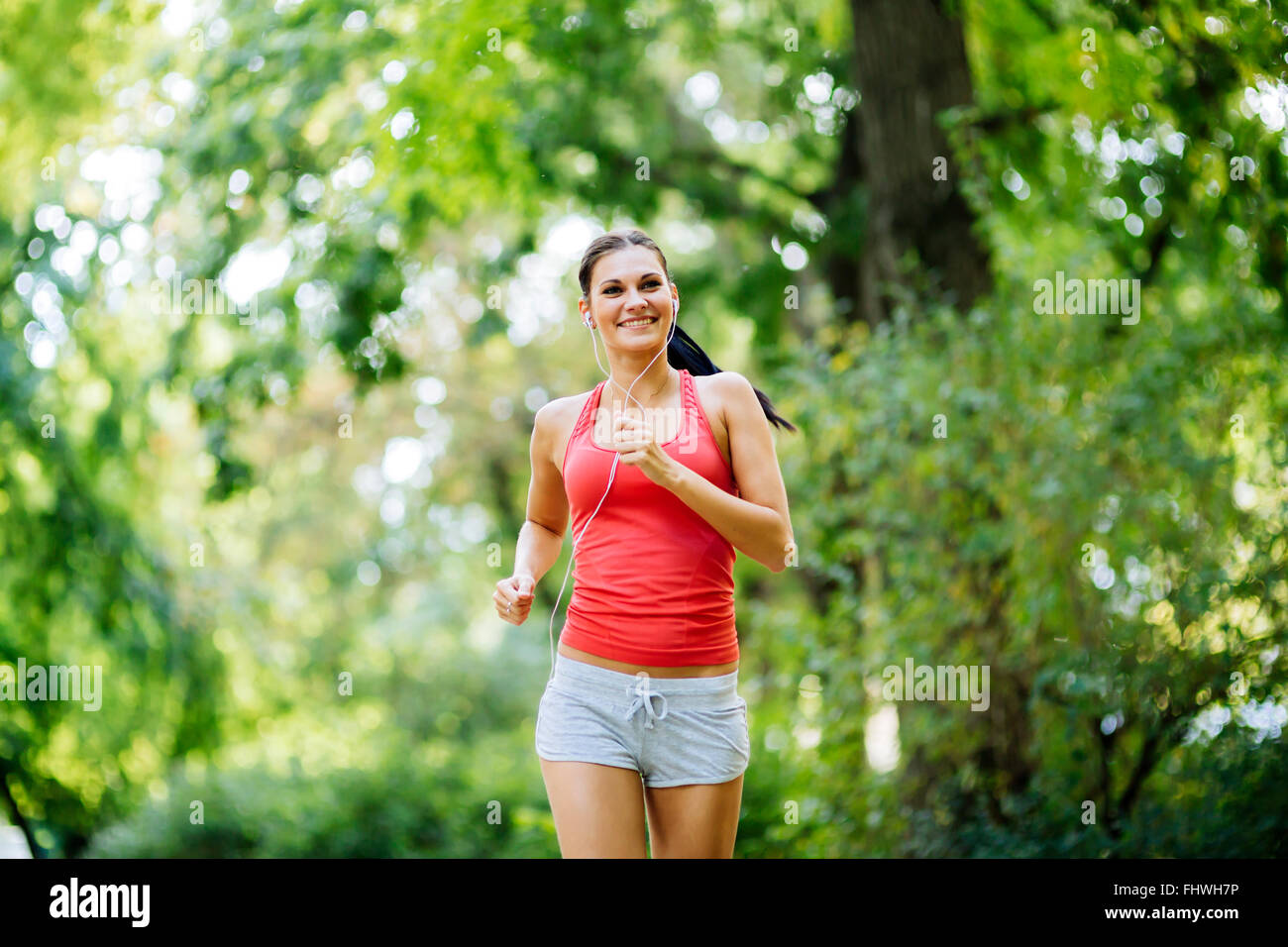 Young beautiful athlete jogging in park and listening to some music while pursuing activity - Stock Image