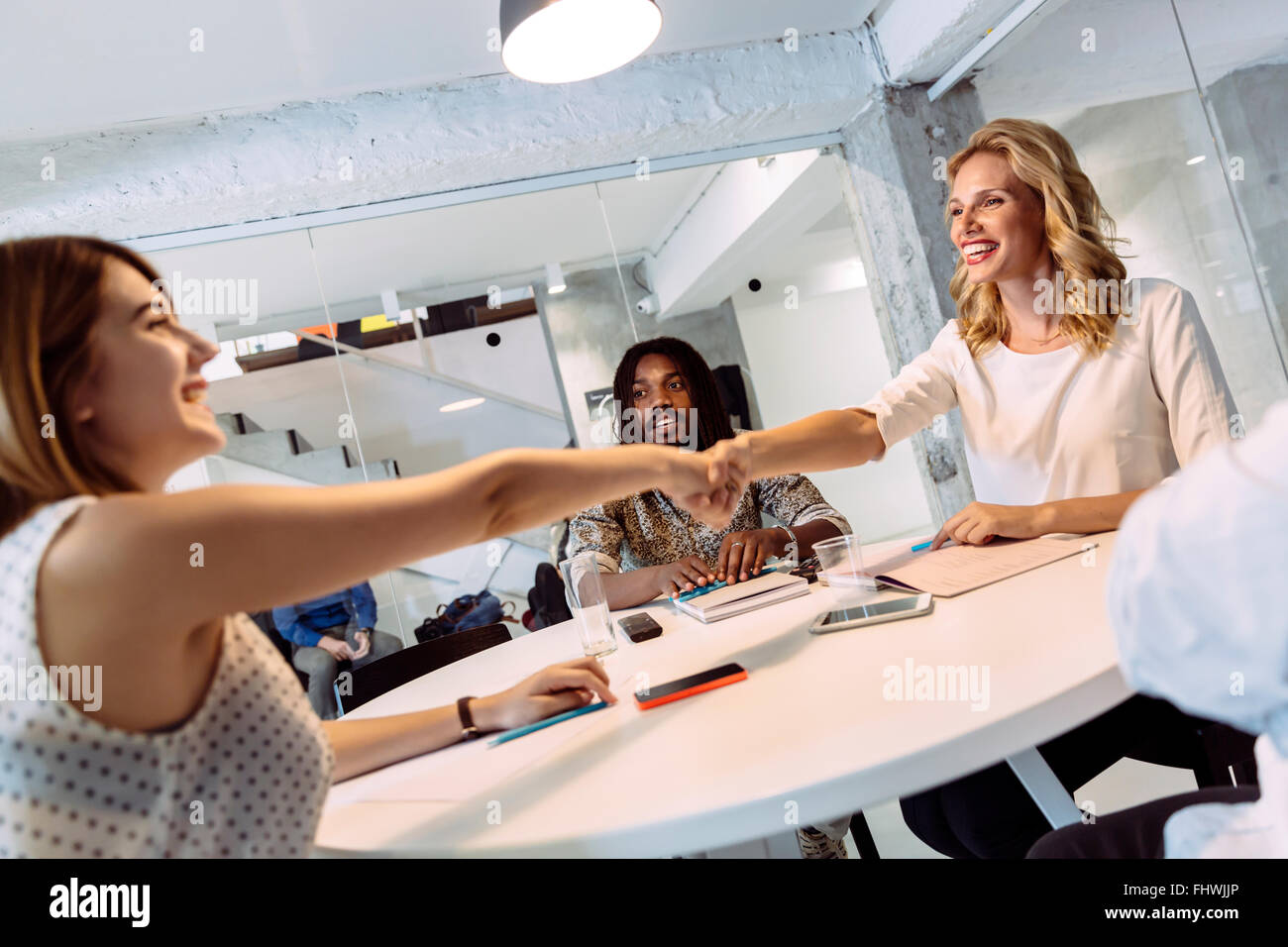 Female coworkers shaking hands and greeting each other while sitting at a table - Stock Image