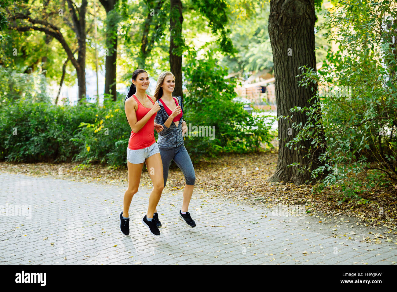 Two young women jogging in nature in pursuit of a perfect body figure - Stock Image