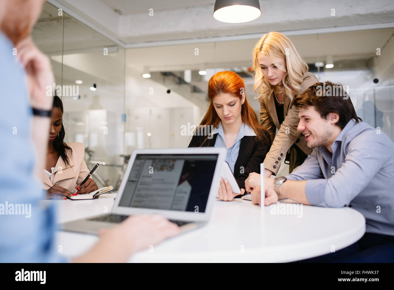 Businesspeople working in office and sharing ideas - Stock Image