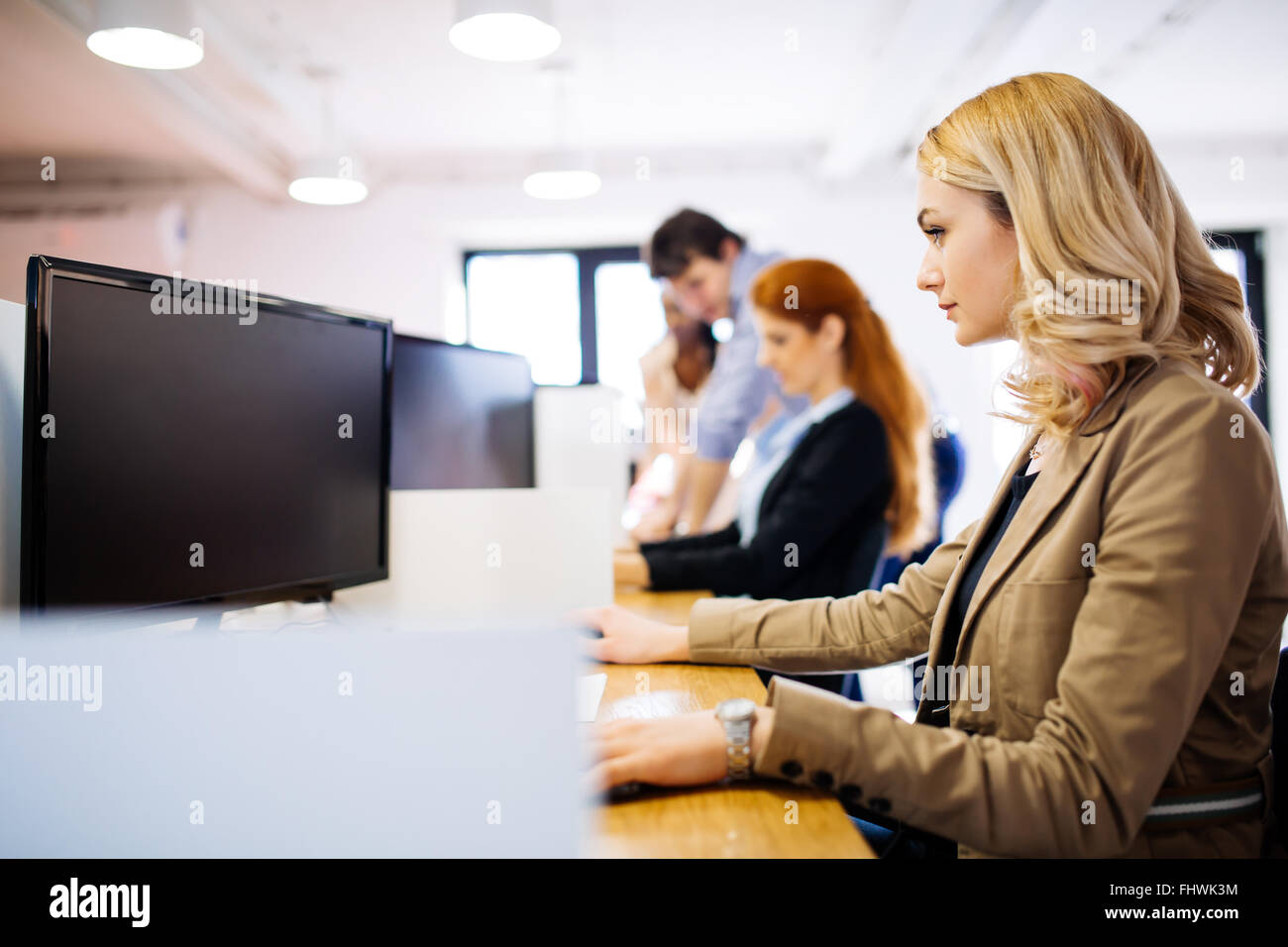 Businesswoman using computer in office while sitting at desk - Stock Image
