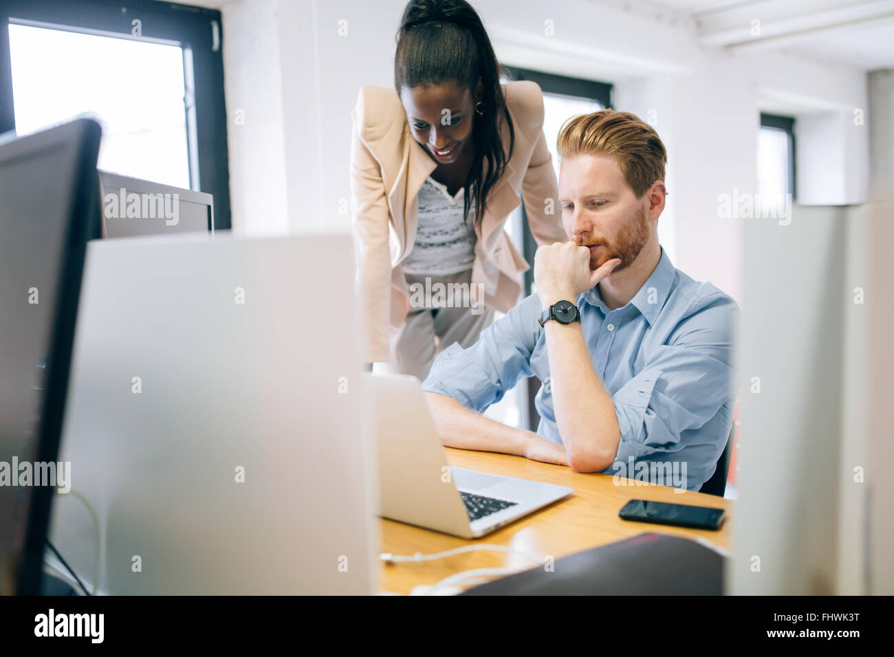 Supervising colleague during work in office - Stock Image