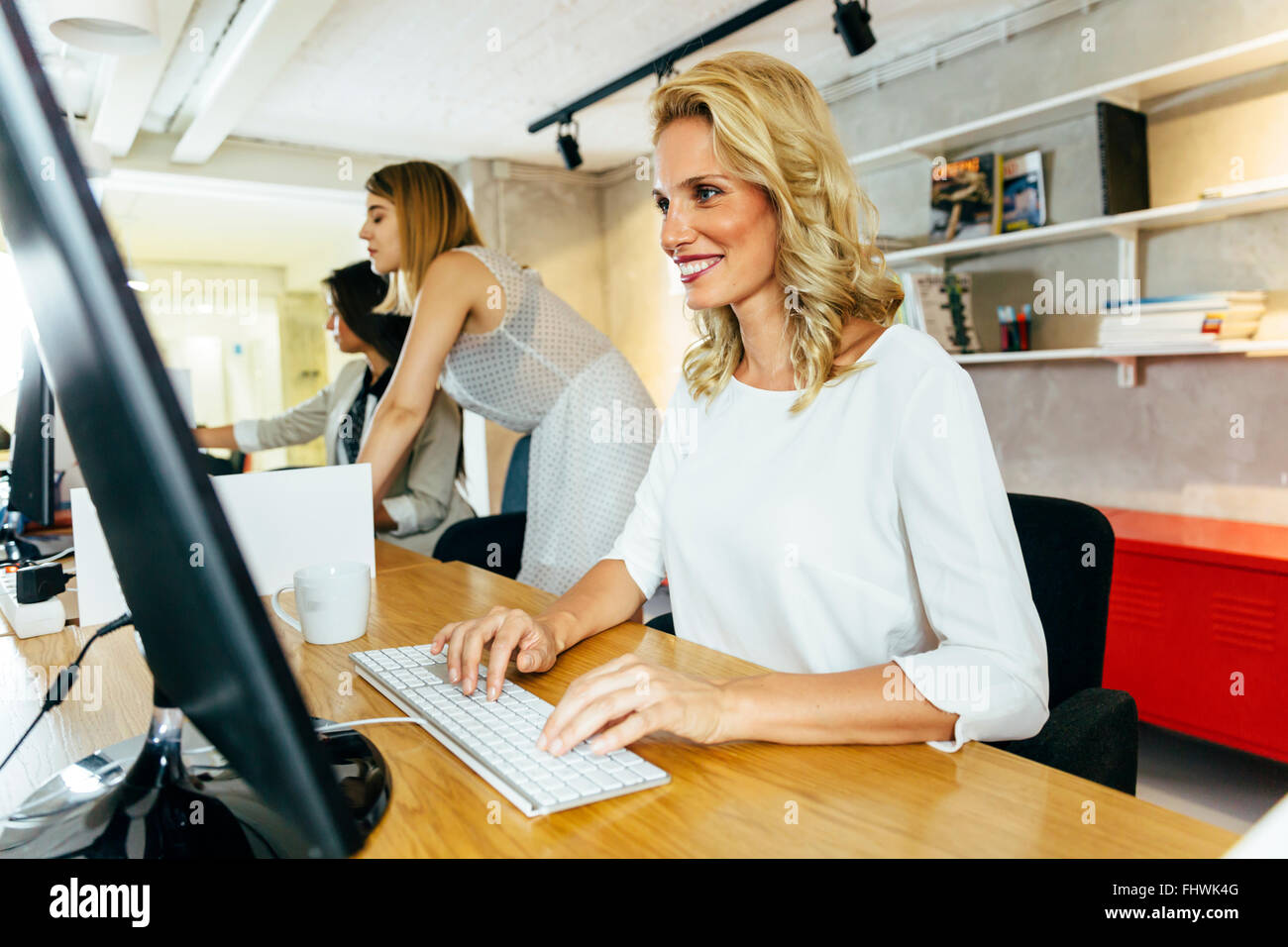 Beautiful woman working in a modern office while sitting in front of a desktop - Stock Image