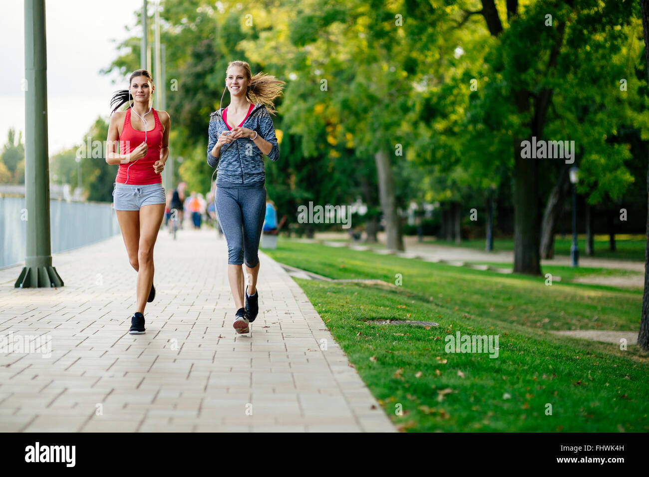 Two women jogging in park and listening to music - Stock Image