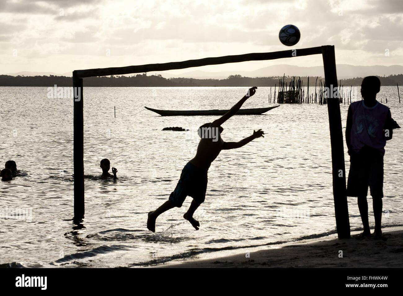 Boys playing ball on the seafront in Praia de Dentro - Peninsula de Marau Stock Photo