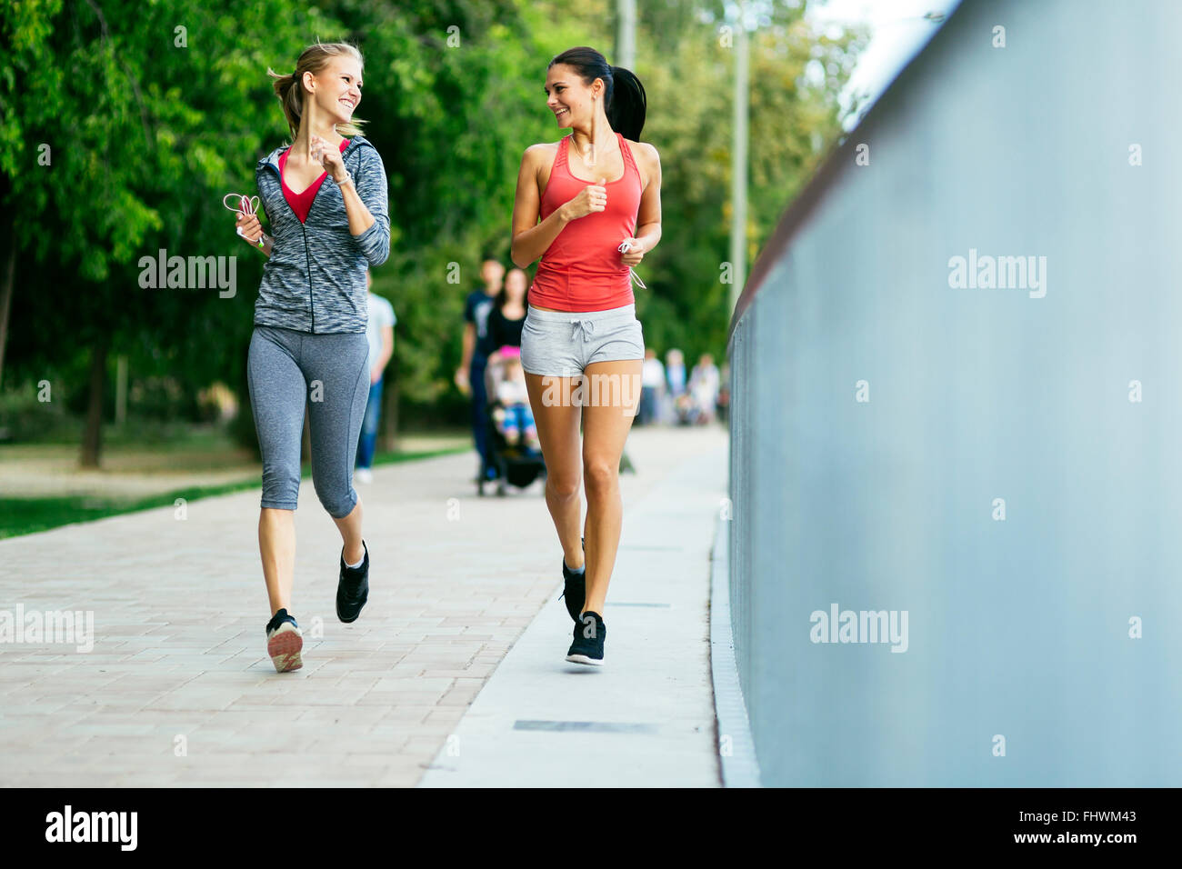 Two sporty women jogging in city while listening to music - Stock Image