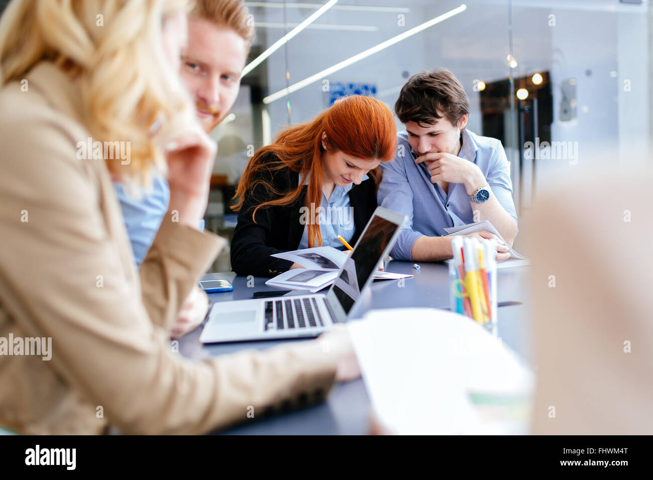 Business people collaborating in office and working on project together - Stock Image