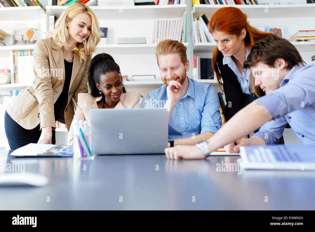 Multiethnic people working in modern well equipped office - Stock Image