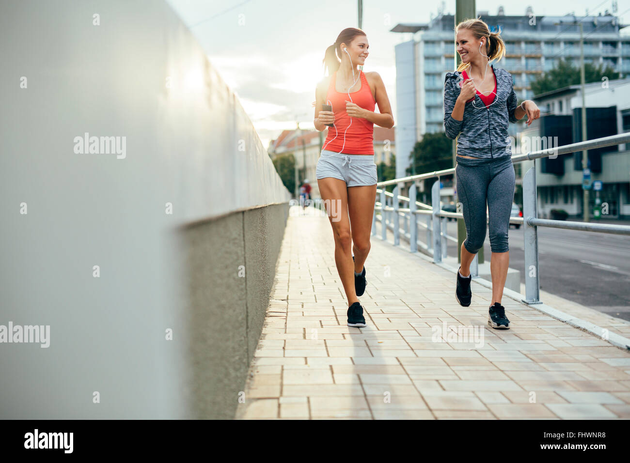 Beautiful women jogging in city while sun is setting down - Stock Image