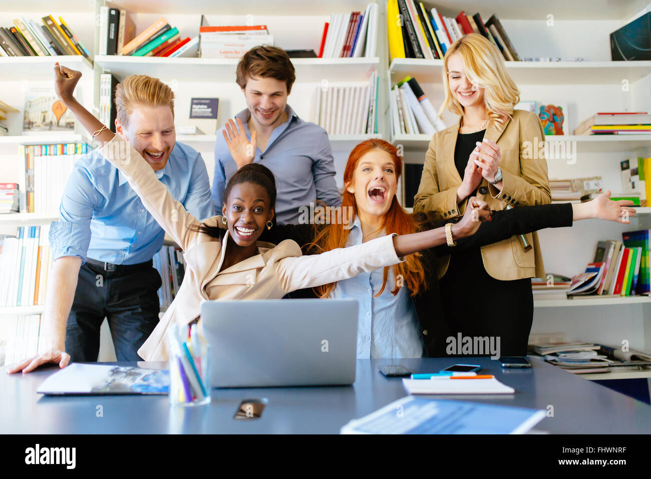 Successful company celebrates business success with coworkers being happy - Stock Image