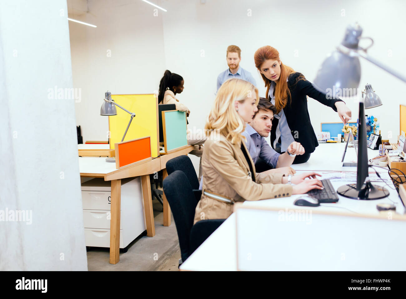 Coworkers solving problems together in modern office - Stock Image