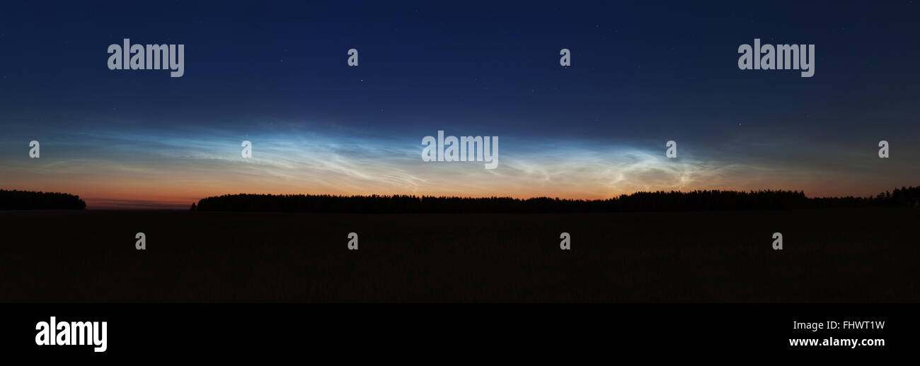 Beautiful sky phenomenon noctilucent clouds sunset landscape panorama photo - Stock Image