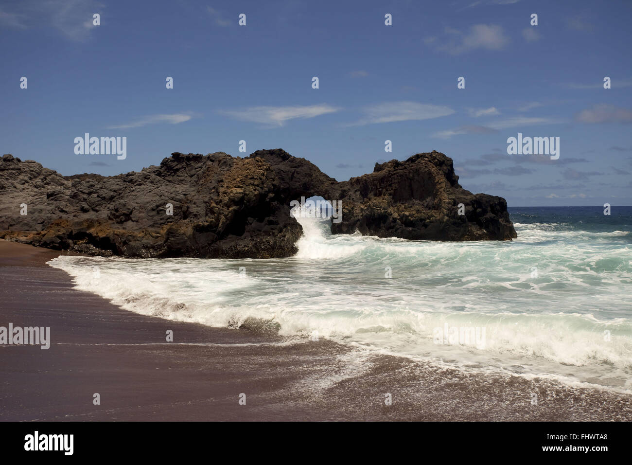 Volcanic rock pierced by the force of the water on the island of Trinidad in the Atlantic Ocean - Stock Image