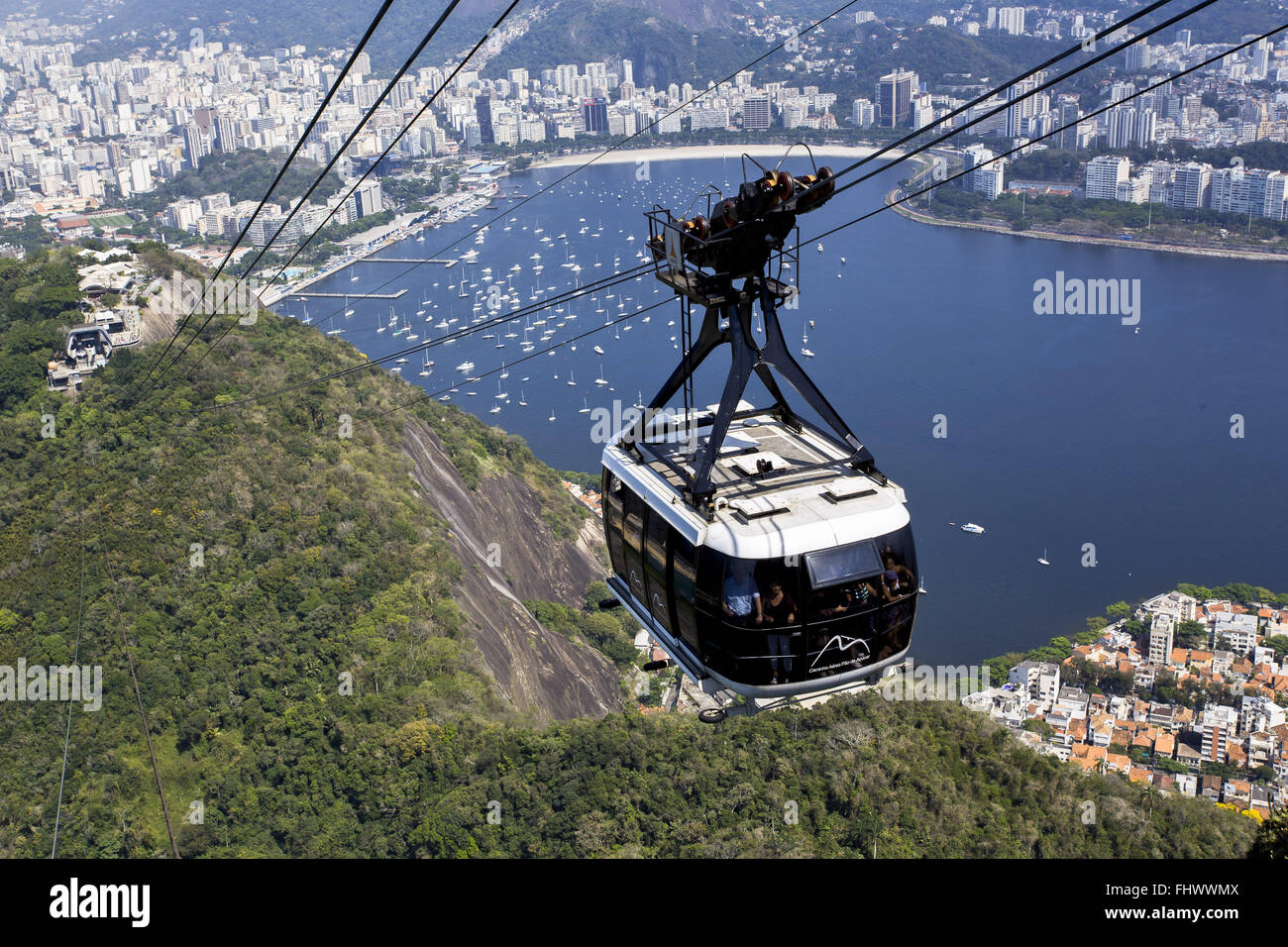 Monorail leaving Morro da Urca toward the Pao de Acucar - Botafogo Beach and Inlet Incidental Stock Photo