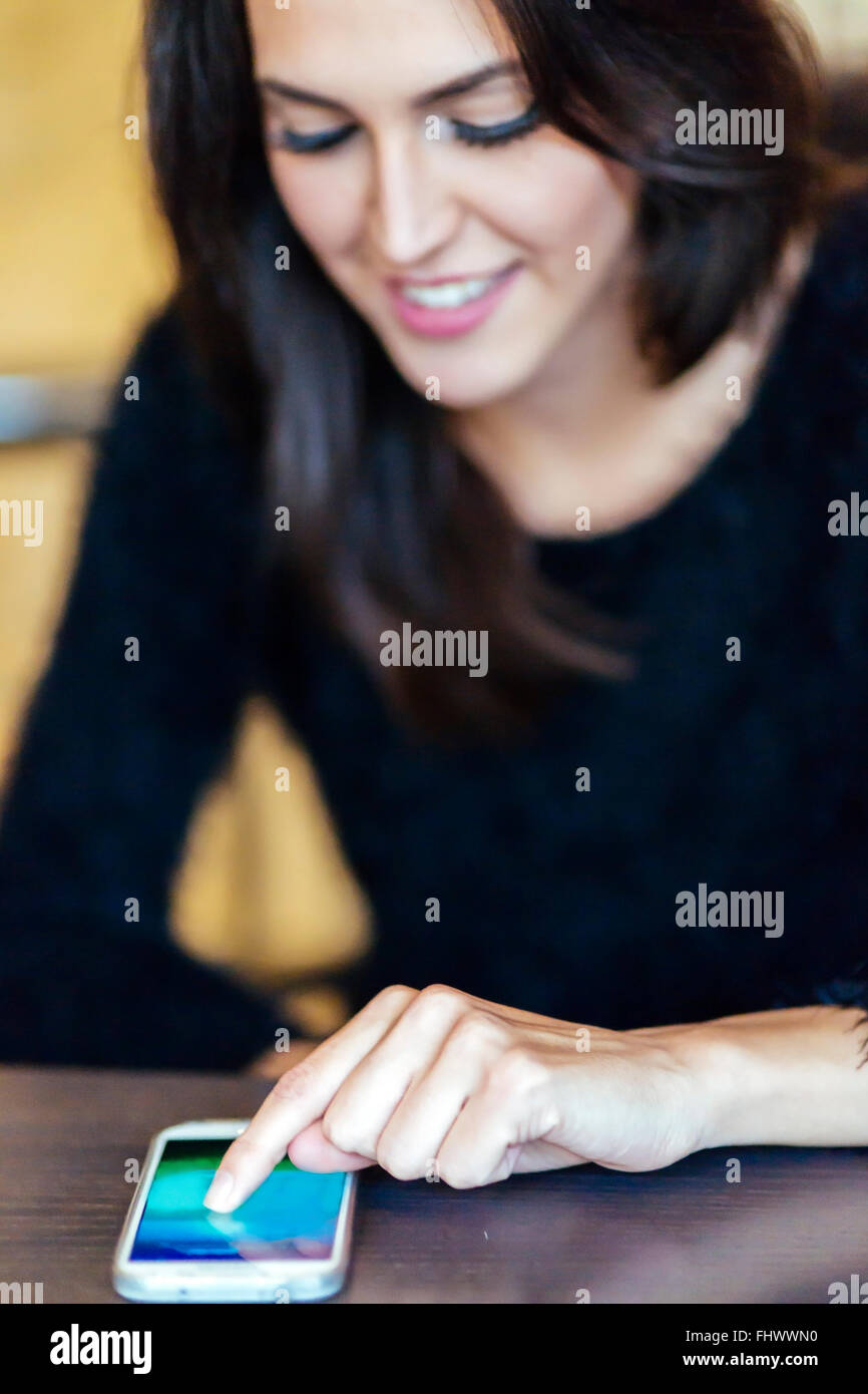 Beutiful brunette tapping phone - Stock Image