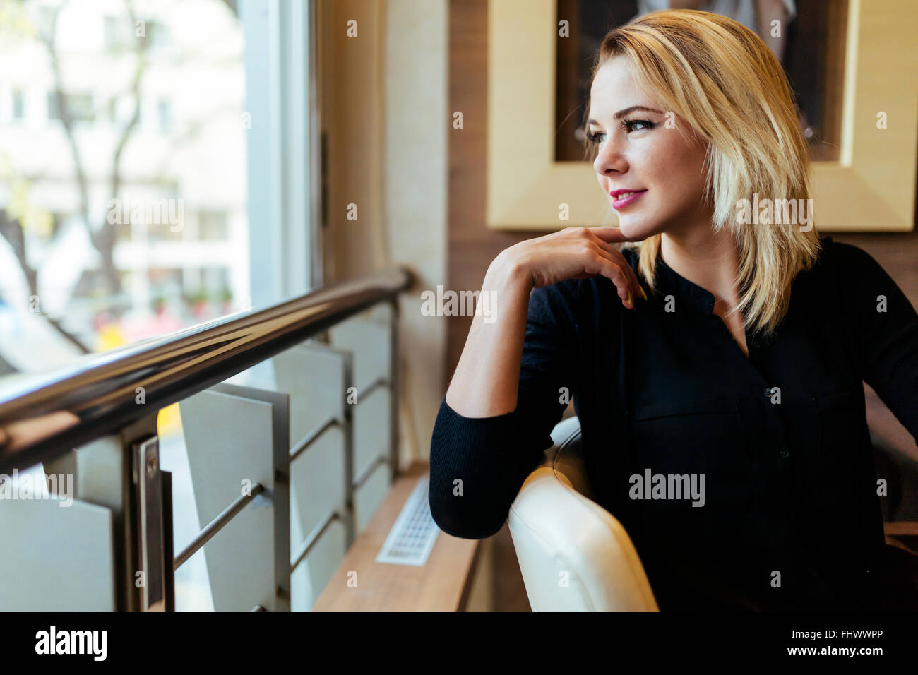 Blonde businesswoman looking out the window - Stock Image