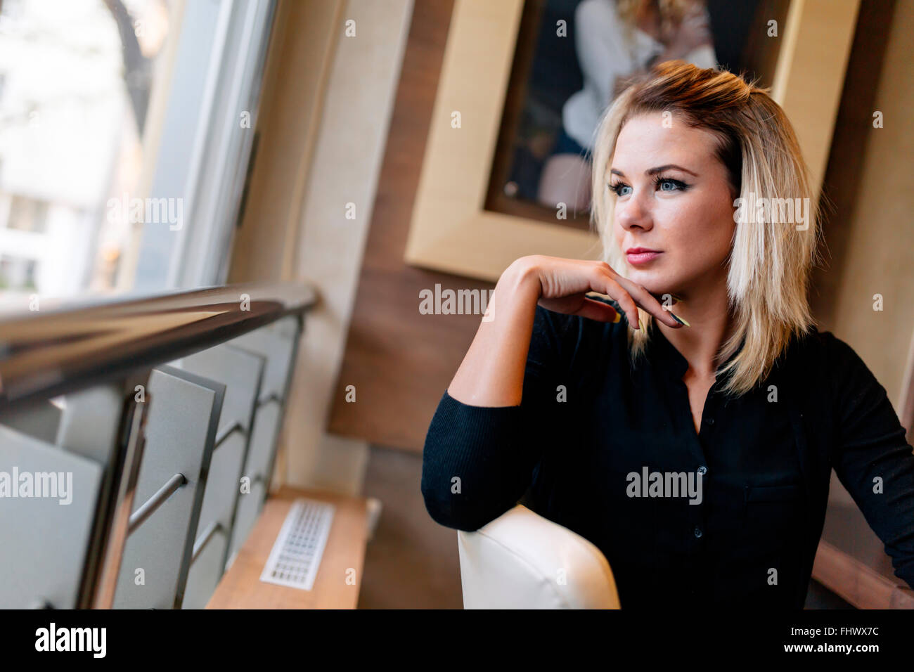 Beautiful woman looking out the window and having a break - Stock Image