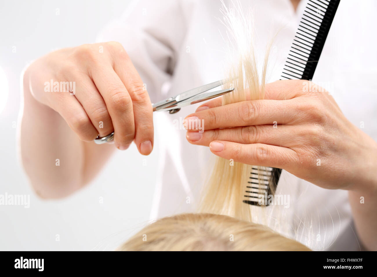 Barber haircut woman in a hair salon. Undercutting the split ends of hair - Stock Image