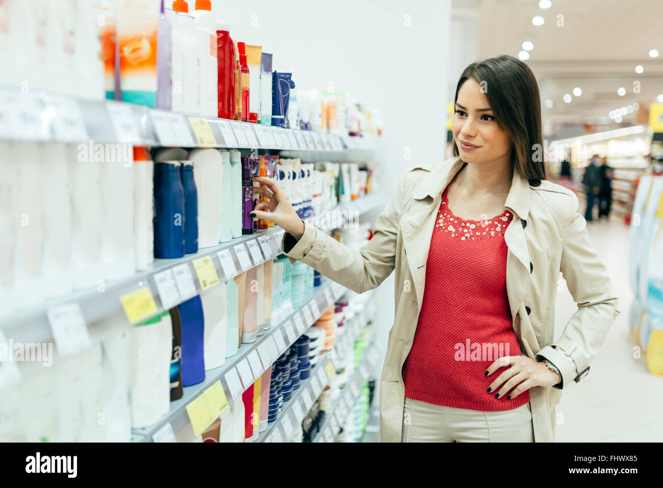 Beautiful woman buying body care products in supermarket - Stock Image