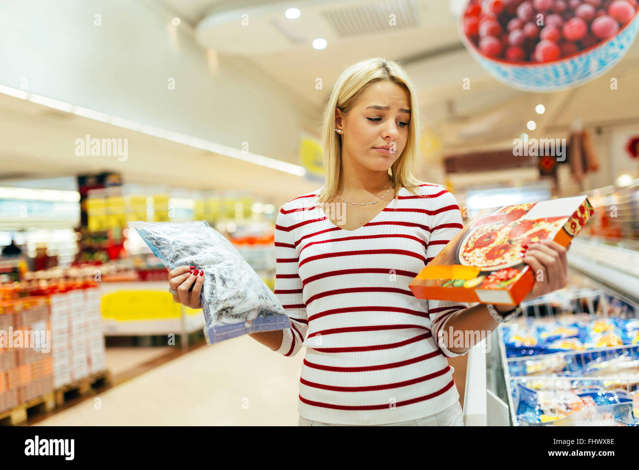 Beautiful woman deciding what to buy based on what is healthier - Stock Image