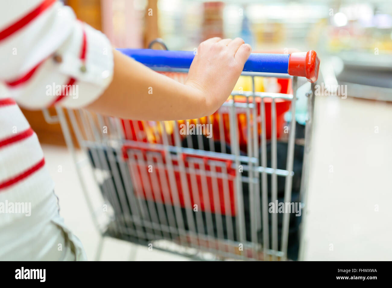 Woman shopping in supermarket and filling shopping cart - Stock Image
