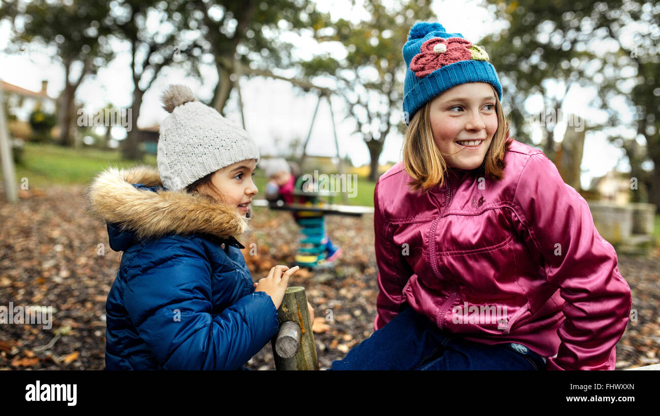 Two girls watching something on a playground in autumn - Stock Image
