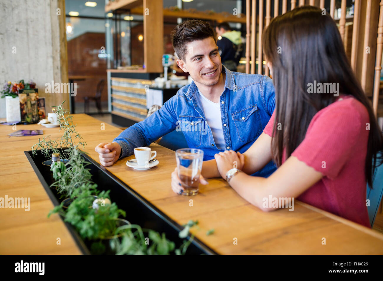 Happy young couple in restaurant waiting for food and talking - Stock Image