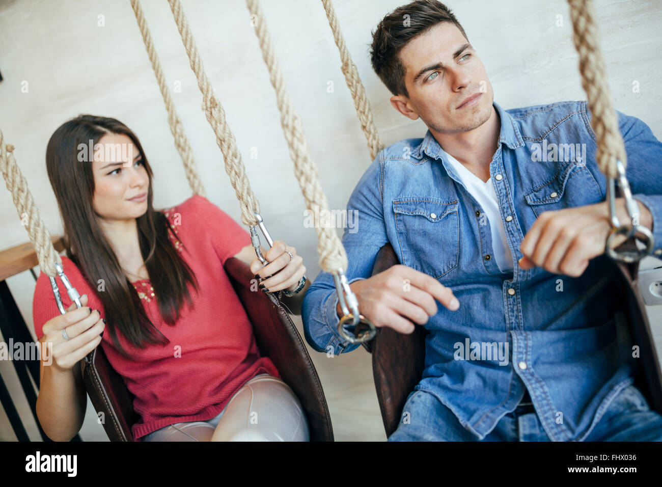 Portrait of couple sitting in swings posing Stock Photo