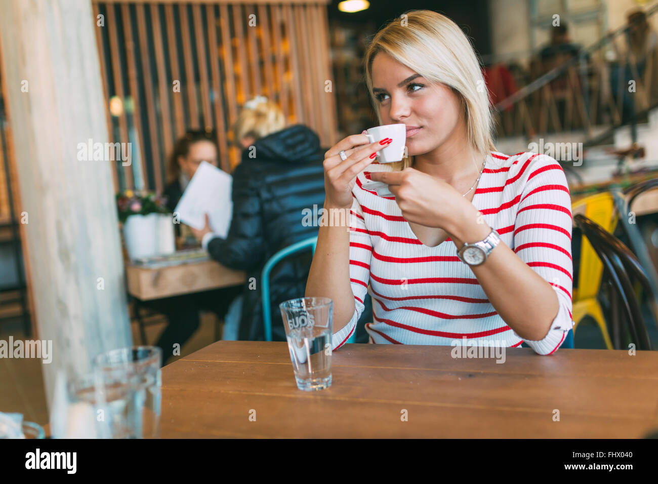 Beautiful woman drinking coffee in a wooden cafe - Stock Image
