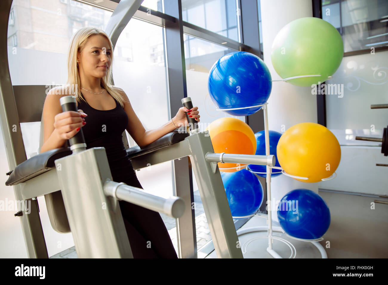 Beautiful woman training in gym and keeping body in shape - Stock Image