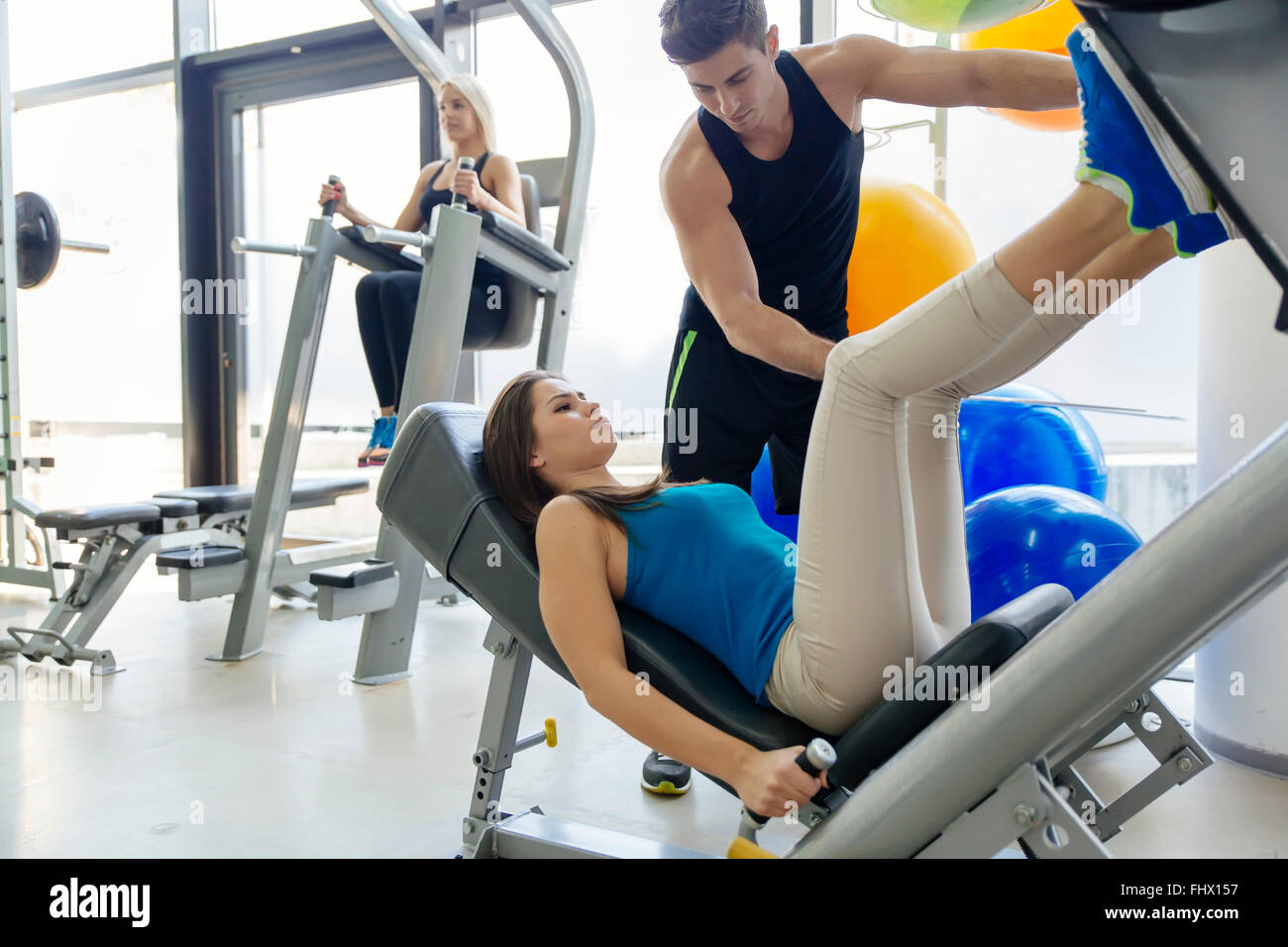 Beautiful woman doing leg exercises in gym with the help of personal trainer - Stock Image