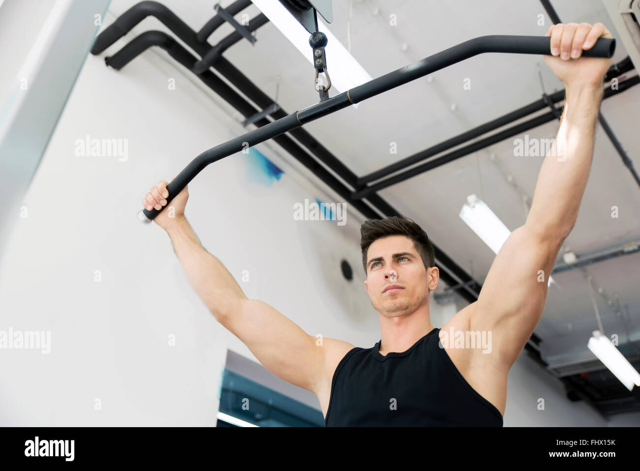 Handsome man working out in gym - Stock Image