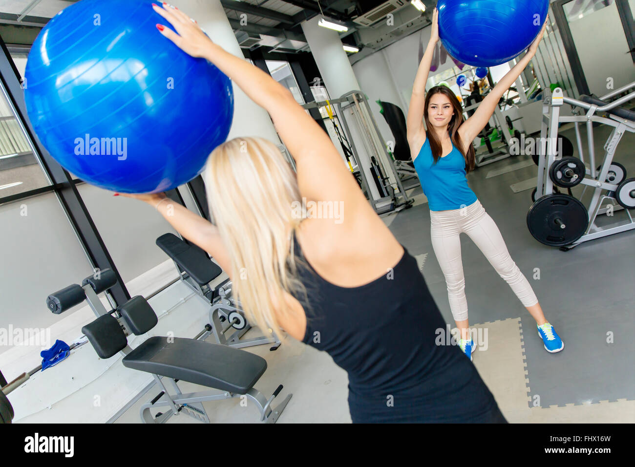 Women, friends training in gym and stretching muscles with medicine ball - Stock Image