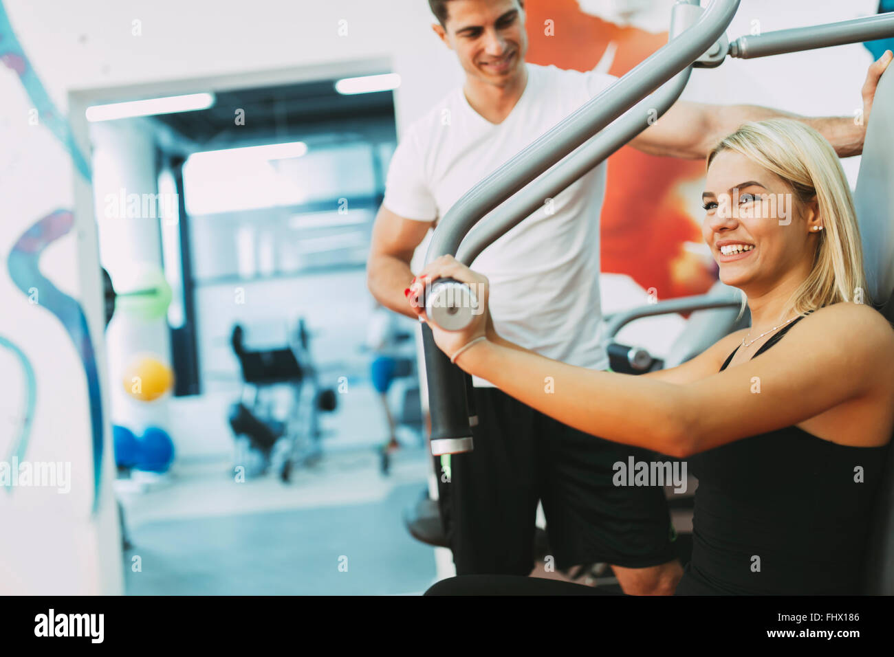 Beautiful woman exercising in gym with some help by personal trainer - Stock Image