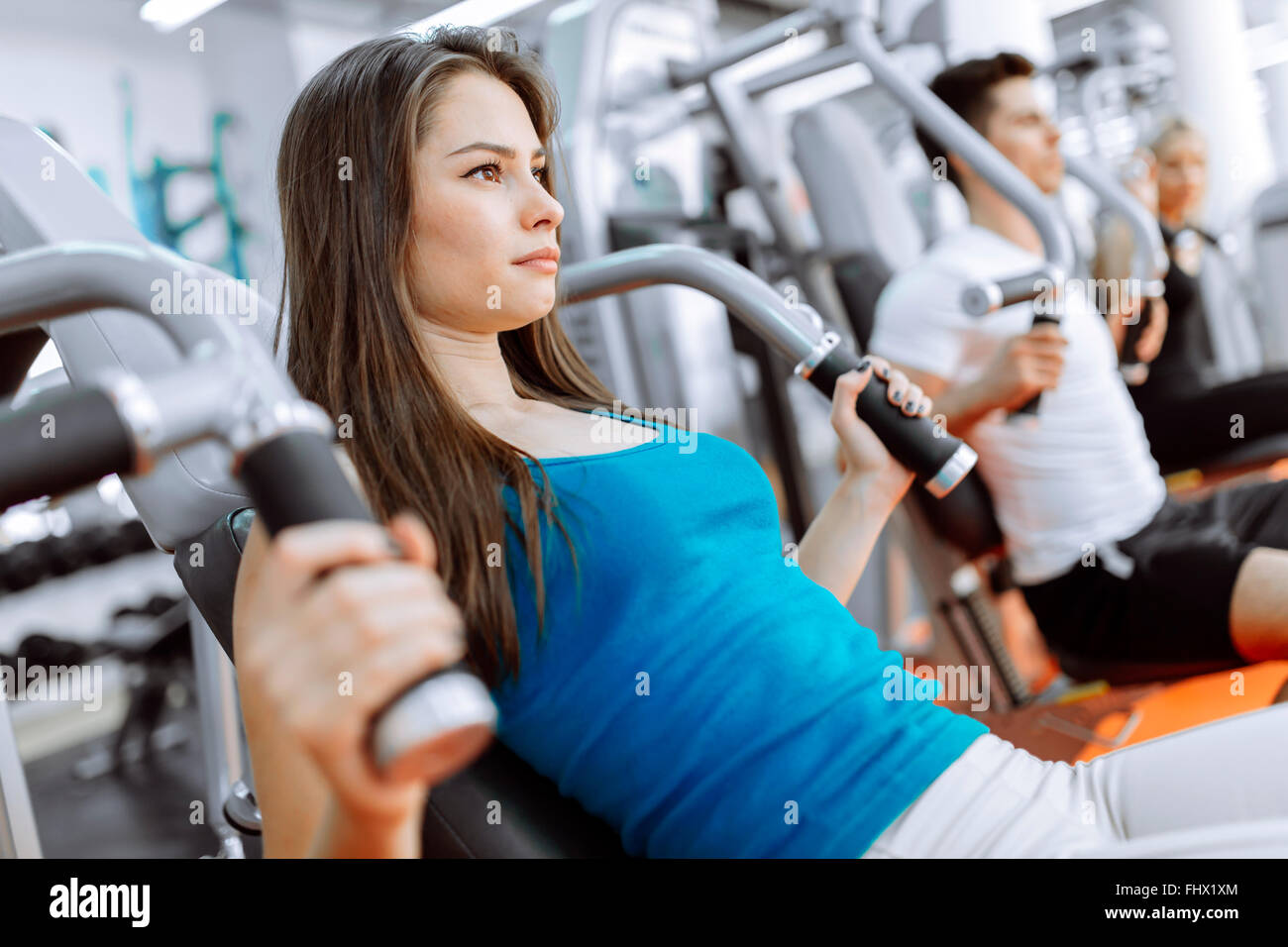 People exercising in gym on various machines - Stock Image