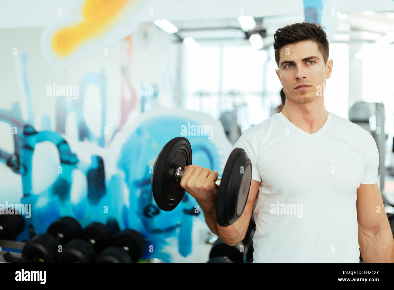 Handsome man lifting weights in gym and staying fit - Stock Image