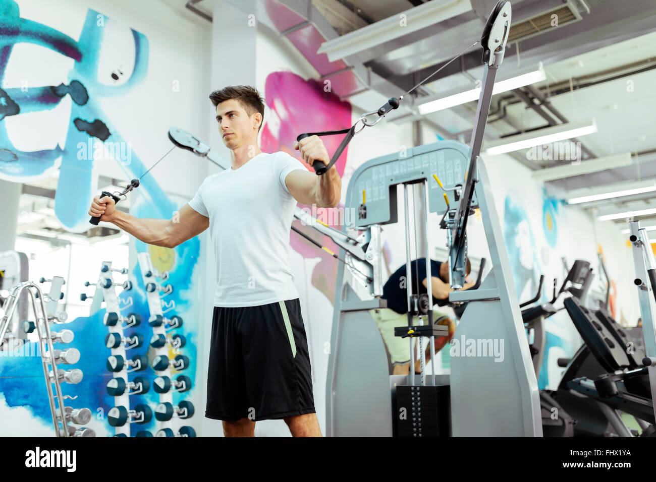Handsome man training in clean modern gym on various machines - Stock Image
