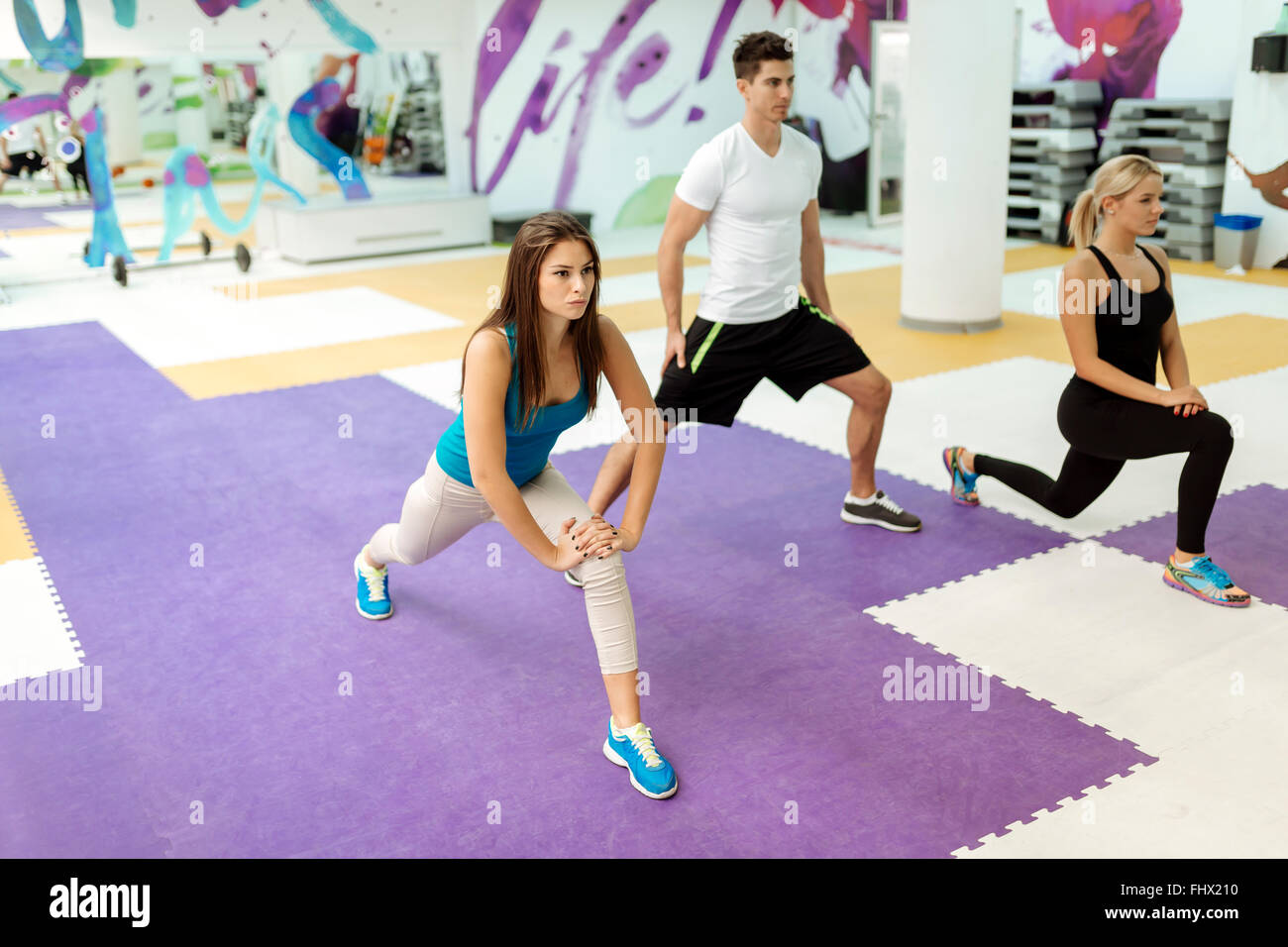 People exercising in fitness club with the help of personal trainer - Stock Image