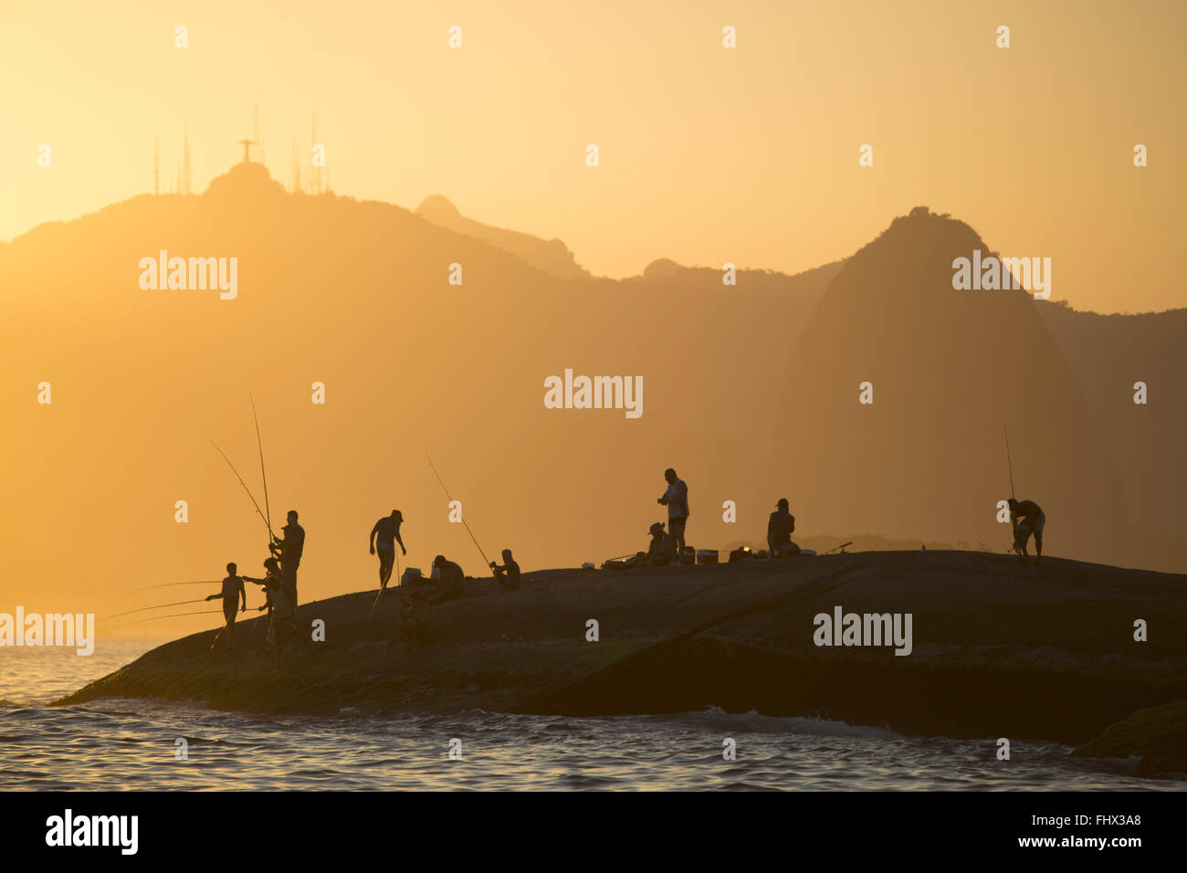 Fishermen on the rocks between the oceanic beaches Quiet and Camboinhas - Stock Image