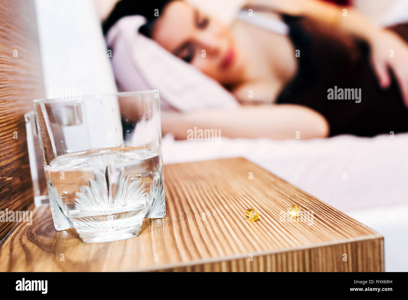 Pregnant woman resting with pills at hand for various aches - Stock Image