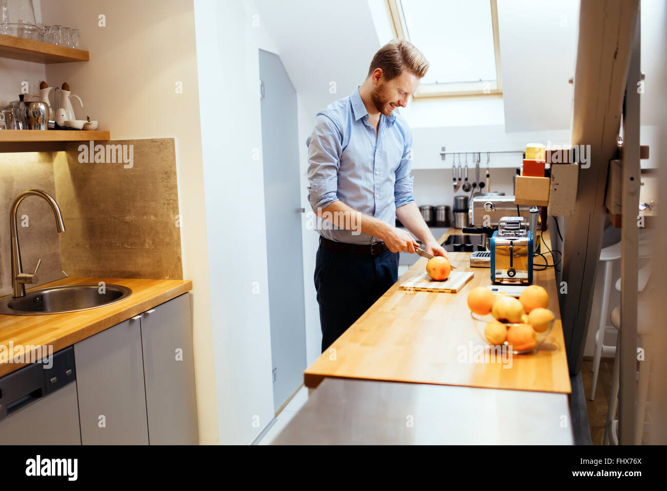 Man slicing oranges in kitchen with knife - Stock Image
