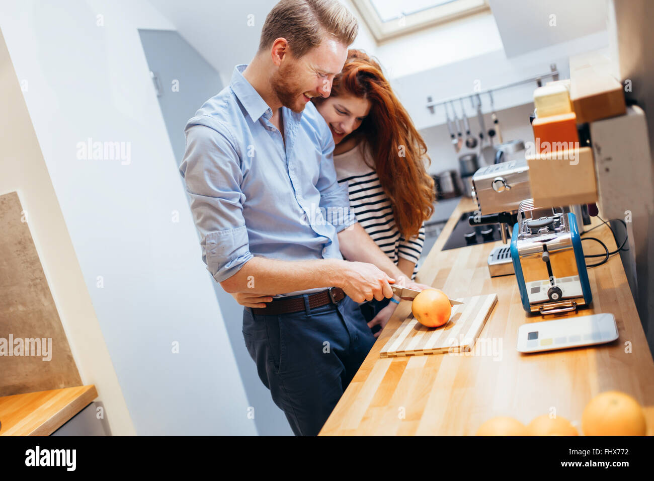 Happy couple making healthy organic juice in kitchen - Stock Image
