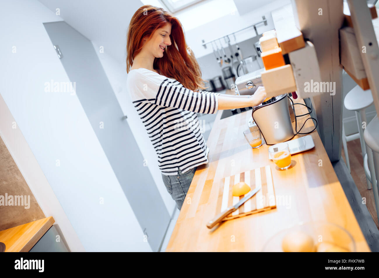 Beautiful woman squeezing oranges in order to prepare hommade juice Stock Photo