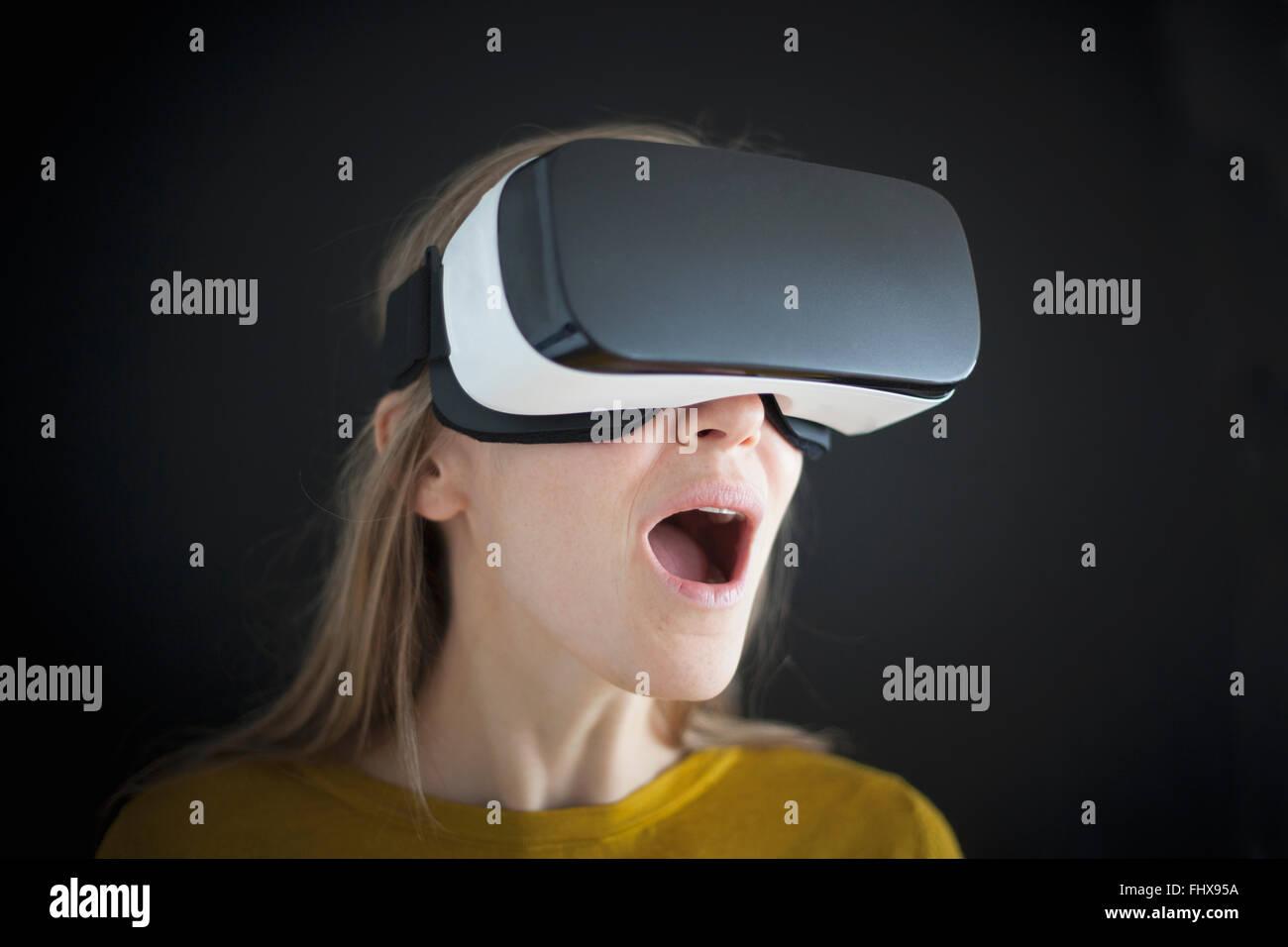 Astonished woman wearing Virtual Reality Glasses - Stock Image