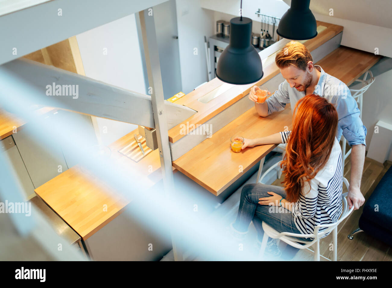 Couple drinking juice in beautiful kitchen and talking - Stock Image